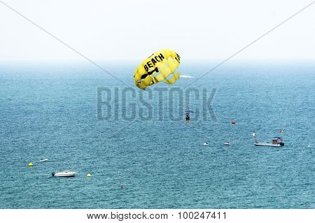 LAGOS, PORTUGAL - AUGUST 18, 2015: Parasailing near sea beach. Parasailing is a popular recreational activity among tourists in Portugal.