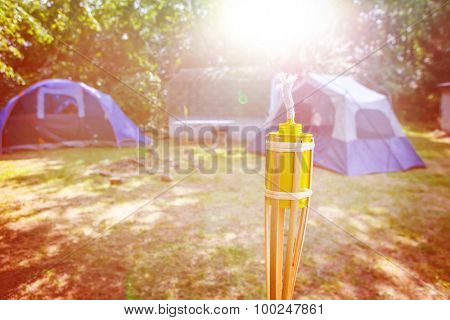 Tent campsite in the early morning sunlight. Focus on wick of torch.
