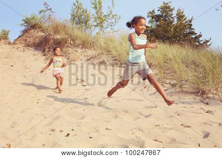 Happy Smiling girls running down the dunes at the beach. Some motion blur on girls.
