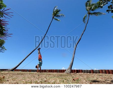 Man Handstanding In The Grass Along Cliff Shore Next To Shallow Ocean Waters Of Waikiki