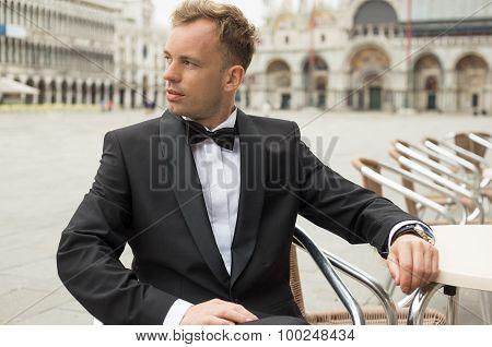 Man in tuxedo sitting in St Mark's Square in Venice