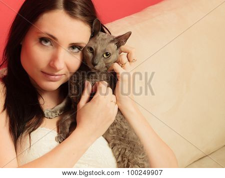 Woman On Sofa Playing With Cat