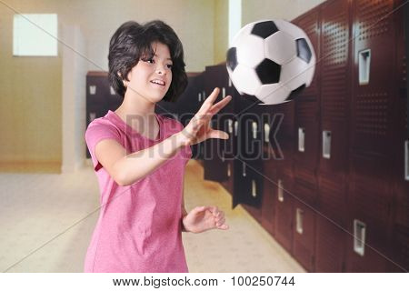 A pretty young teen playing with a soccer ball in her school's locker room.  Motion blur on the ball.