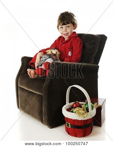 An adorable preschooler sitting in a plush chair in her red pajamas.  She holds a doll in a Christmas dress and a basket of ornaments sits at her side.  On a white background.