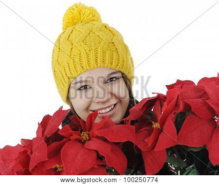 Closeup of a  pretty teen girl, bundled for winter, happily carrying a bundle of red poinsettias.  On a white background.