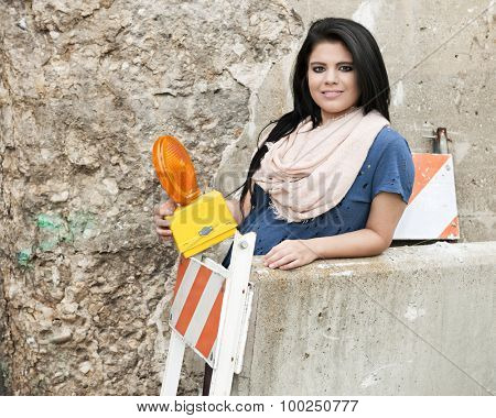 A pretty teen girl holding a caution light while  standing behind orange and white striped and  concrete barriers.   Space on the concrete barrier and crumbling wall behind her for your text.