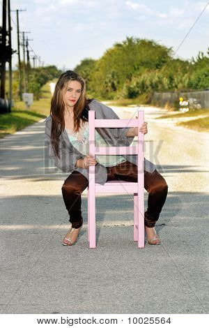 Teen Girl Sitting in a Chair in a Roadway (1)