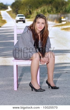 Teen Girl Sitting in a Chair in a Roadway (2)