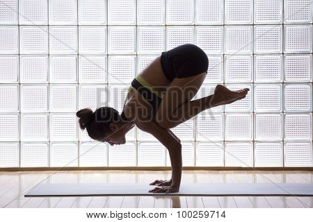 Young woman practicing crow pose in a yoga studio indoors