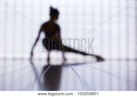 Blurred image of a young woman practicing in a yoga studio.