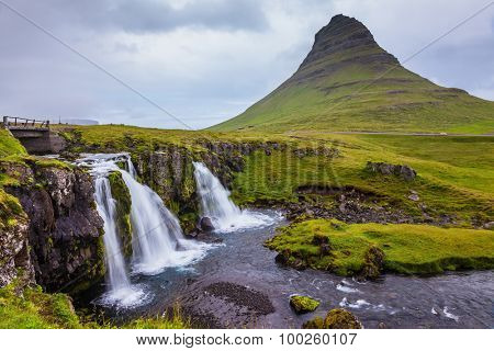 Threaded full-flowing waterfall on the grassy mountains. Iceland - country of mountains, rivers and waterfalls