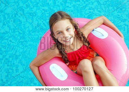 9 years old child playing in the swimming pool on inflatable ring