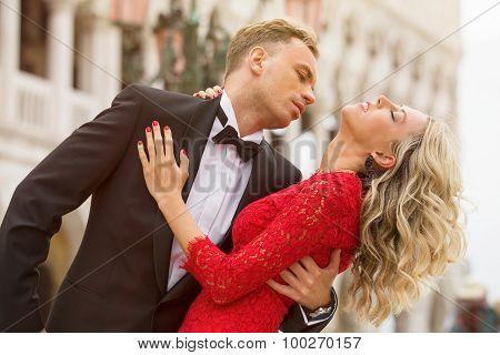 Elegantly dressed couple dancing outside