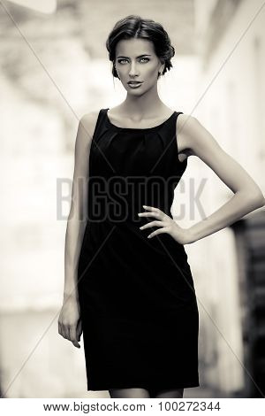 Black-and-white portrait of a vogue model in black dress posing over urban background. Fashion shot.