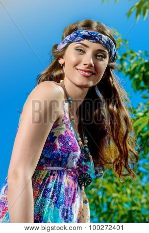 Romantic hippie girl standing outdoor in the summer day over blue sky background. Hippie style. Child of nature.