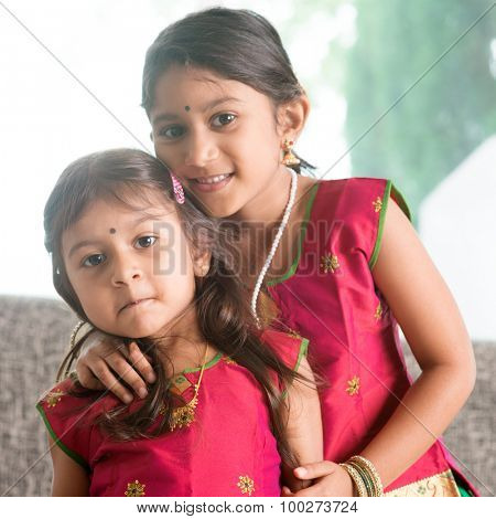Indian girl hugging her younger sister with love. Asian children at home. Beautiful daughters in traditional India sari.