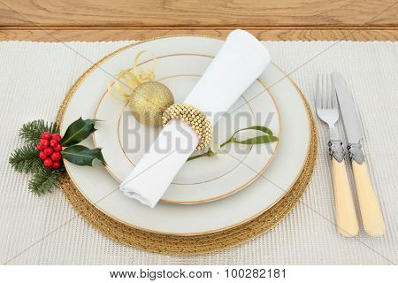 Christmas dinner place setting with plates, napkin, antique cutlery, gold bauble, holly, mistletoe over silver table runner on oak background.