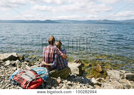 Rear view of amorous romantic couple in embrace sitting by the sea