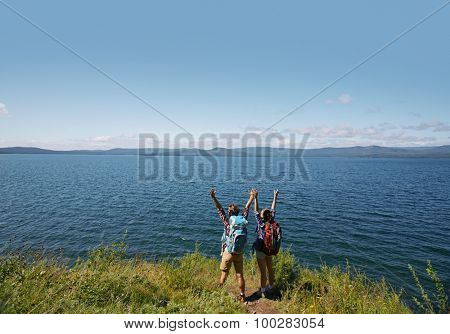 Ecstatic hikers with raised arms standing by the sea