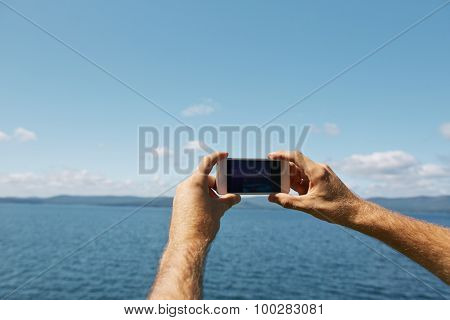 Human hands with cellphone making photo of the sea and skyline