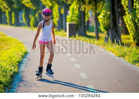 Rollerblading. Roller skating young girl in park rollerblading on inline skates.