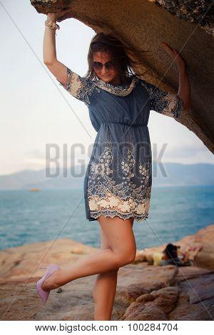 Brunette Girl In Short Grey Frock Stands Under Rock Against Sea