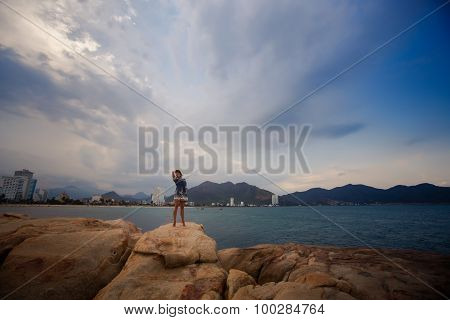 View Of Girl In Short Frock On Rocks At Distance Against Sea