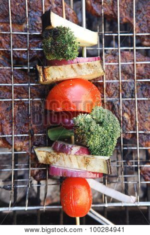 fresh beef steak fillet mignon on meat holder over charcoal grid with vegetable shish kebab tomato broccoli,red onion on skewer ready to prepare for outdoor party