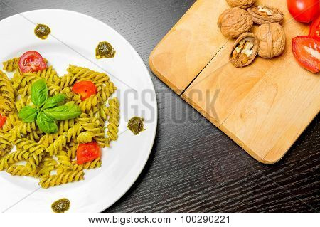 Top Of View Of Dish Of Pasta With Pesto Genovese Sauce And Vegetables, Tomato And Basil On Black Woo