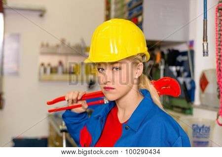 young mechanic with yellow helmet and wrench in a workshop. rare female occupations.