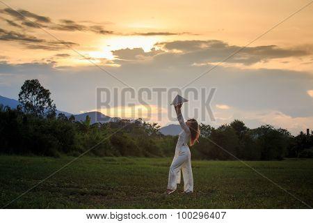 Blonde Girl In Vietnamese Dress Lifts Hat Above Head On Field