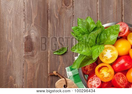 Fresh colorful tomatoes and basil in colander. Top view with copy space