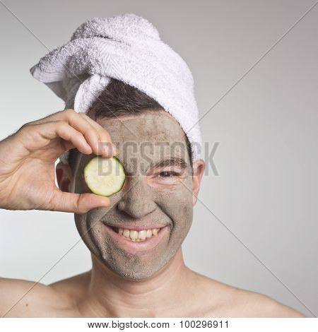 Handsome Man With Clay Facial Mask In Beauty Spa