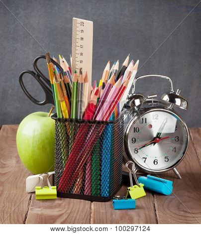 School and office supplies, alarm clock and apple on classroom table