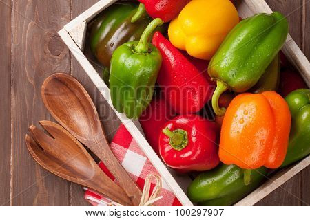 Fresh colorful bell pepper in box on wooden table. Top view