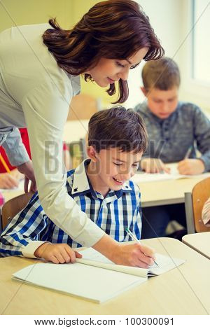 education, elementary school, learning and people concept - teacher helping school boy writing test in classroom