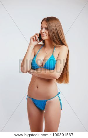 woman in a bathing suit talking phone