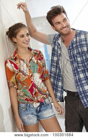 Young couple standing in home under construction, smiling.