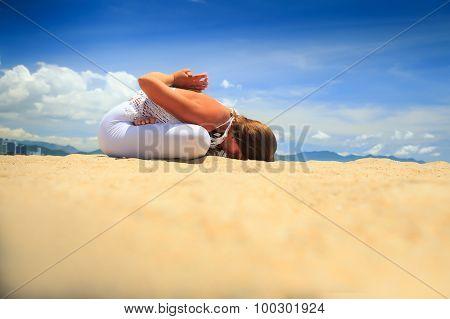 Blonde Girl Sits In Yoga Asana Lotus Forward Bend On Beach