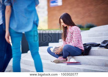 Modern teen girl in casualwear reading book outdoors