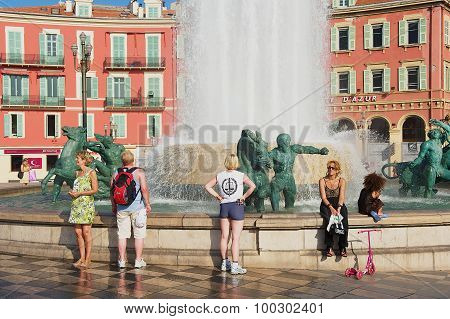 People relax at the Fontaine du Soleil at the Place Massena square on a hot day in Nice, France.