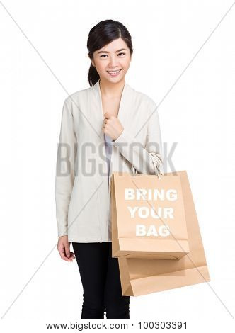 Young woman holding shopping bag and showing bring your bag