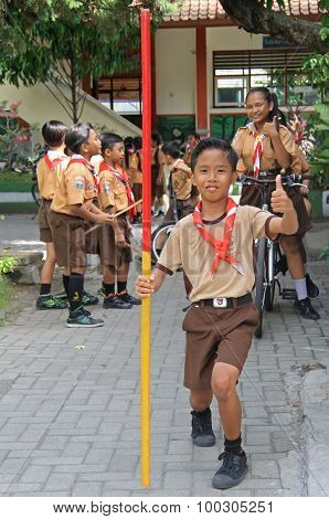boy is holding a stick and showing thumb on the street in Kuta, Bali