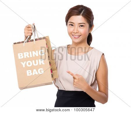 Asian woman finger point to shopping bag and showing phrase bring your bag