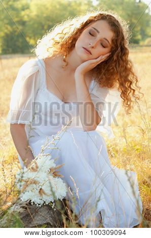 Woman With Curly Golden Hair Resting Her Head On Her Hand