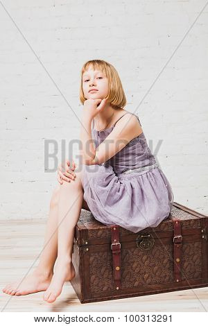 Well-dressed girl sitting on old box