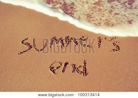 the text summers end written in the sand of a beach