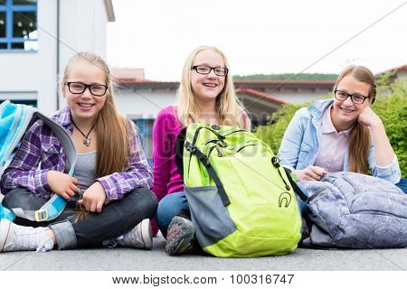 Schoolgirls sitting in schoolyard at school having recess and talking