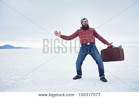 insane widly screaming hipster with awesome beard and retro suitcase making extreme motions on desolate empty salt flats with copyspace composition