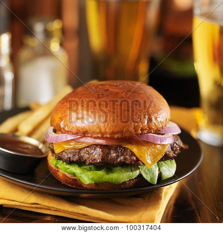 cheeseburger and fries on plate served with beer in background